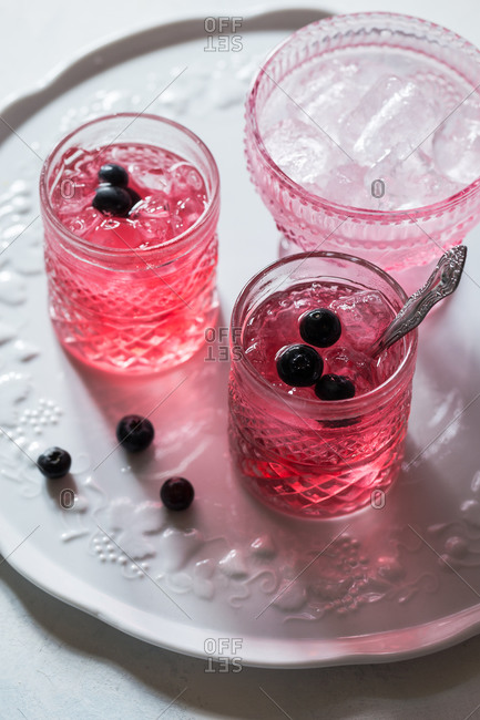 From above of ceramic tray with similar transparent glasses with tasty and healthy pink beverage decorated with fresh blueberries near bowl with ice cubes