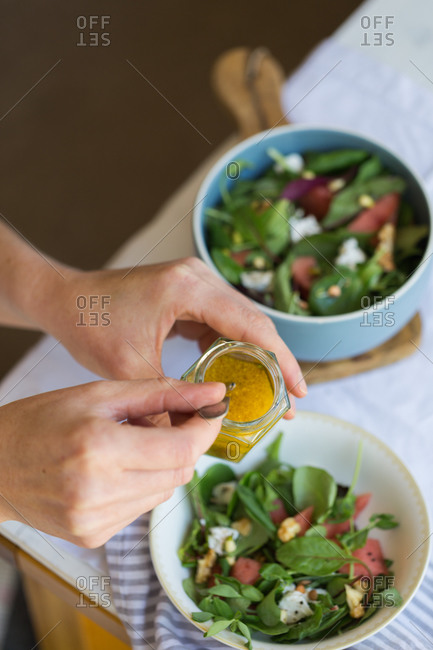 From above of crop anonymous person holding jar glass with sauce for vegetarian salad made of sorrel leaves and fresh watermelon and pitaya slices
