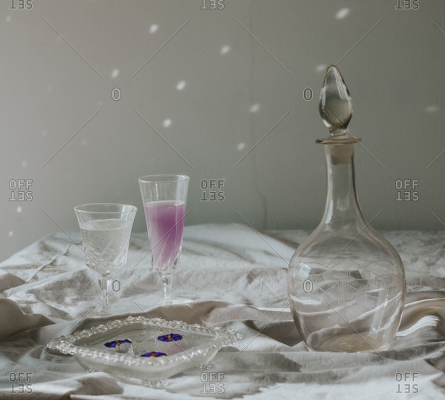 Above view of cocktail decorated with purple flower petals served on white tablecloth with vintage styled glasses and bottle on sunny day