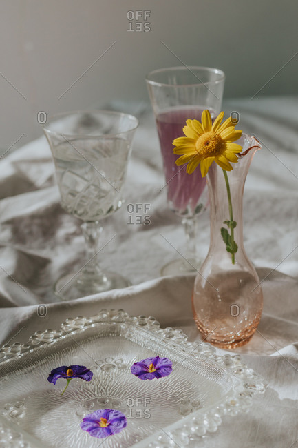 Above view of cocktail decorated with purple flower petals and yellow daisy served on white tablecloth with vintage styled glasses and bottle on sunny day
