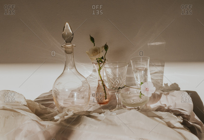 High angle of white delicate flowers in small vase placed on table covered with tulle and arranged with vintage styled glasses and decanter