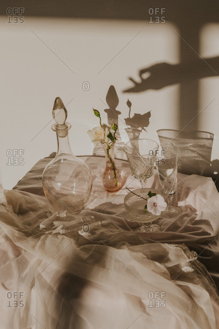 High angle of anonymous person hand shadow on wall over white delicate flowers in small vase placed on table covered with tulle and arranged with vintage styled glasses and decanter