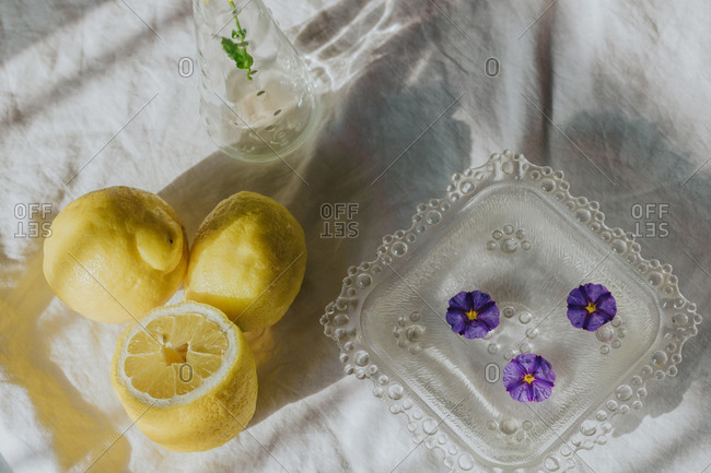 Delicate violet flower in glass vase placed on table with white cloth near refreshing drink and composed with natural lemons