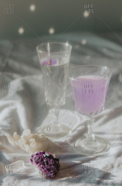 Above view of beautiful composition with natural Quartz and Amethyst placed on white linen tablecloth and glasses of various drinks