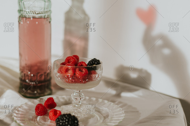 From above bottle of homemade rose wine poured in crystal glass near champagne trumpet and served with plate of fresh raspberries and blackberries against white wall with hand shadow