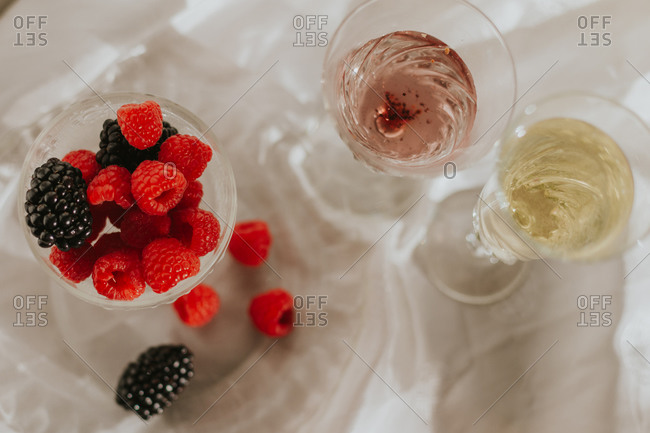From above beautiful composition with vintage styled bottle and glasses on white table arranged with plate and goblet with berries