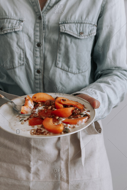 Unrecognizable person in apron standing with bowl of healthy granola with yogurt and fresh fruits