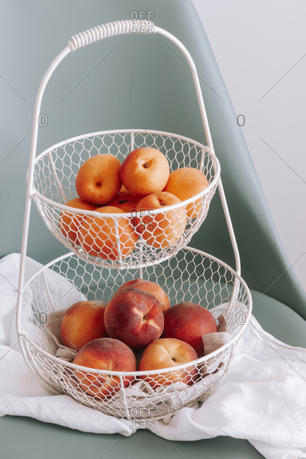 High angle of metal basket with fresh apricots and peaches placed on chair
