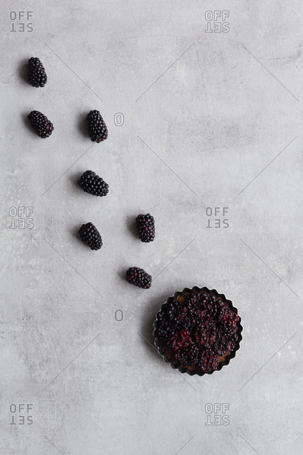 Top view of palatable pie with blackberry arranged in line on table