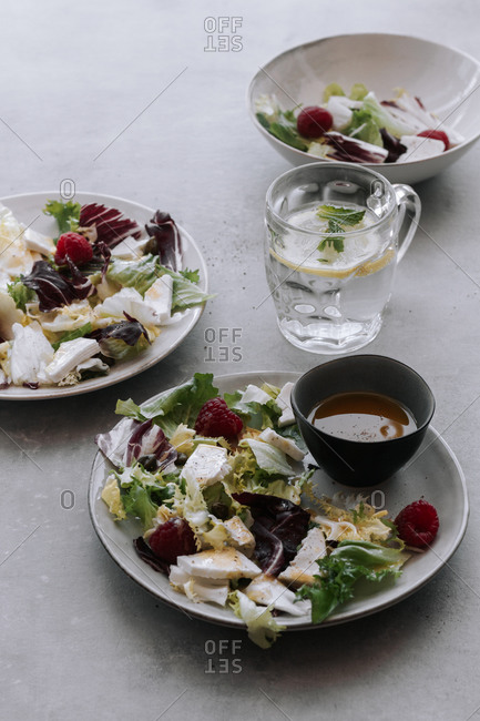 Top view of delicious salad in plates with chopped cabbage and lettuce garnished with raspberries and placed on table with lemon water