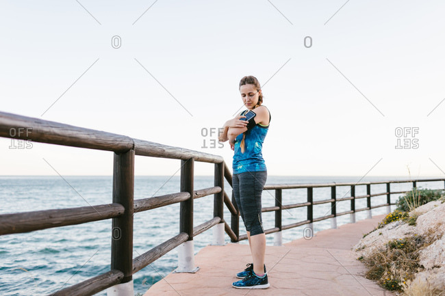 Side view of fit female in sportswear standing on embankment and setting cellphone in armband before workout