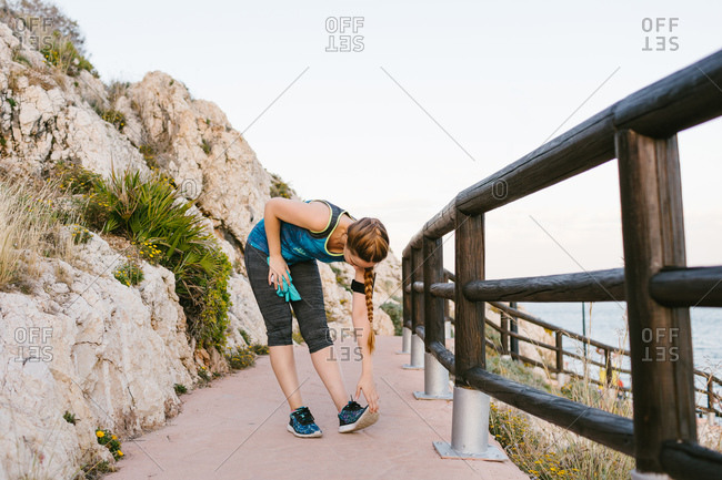 Side view of athletic female warming up and stretching legs during workout on promenade near sea