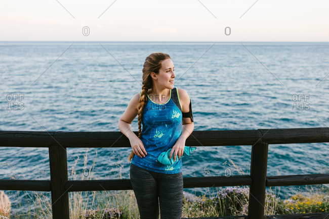Young female standing on embankment contemplating amazing seascape