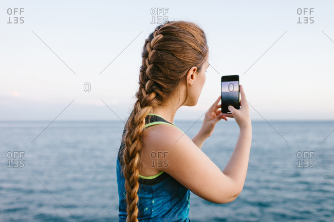 Side view of young female standing on embankment and taking picture of amazing seascape on smartphone