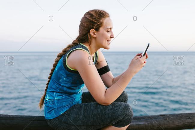 Side view of cheerful sportswoman in activewear sitting on embankment and browsing cellphone after training