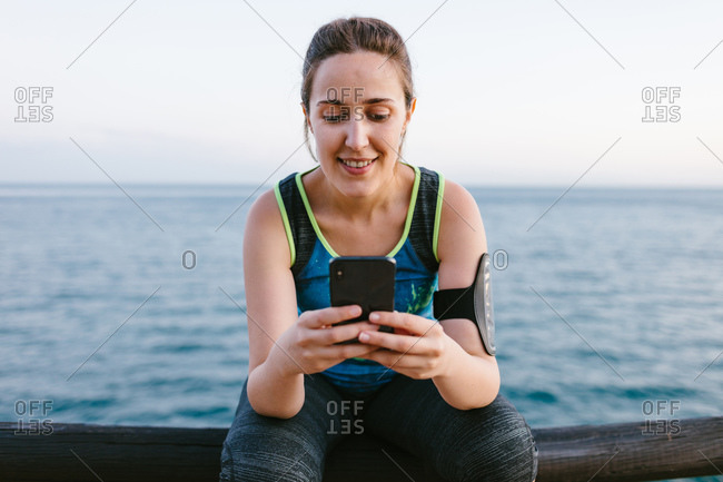 Cheerful sportswoman in activewear sitting on embankment and browsing cellphone after training
