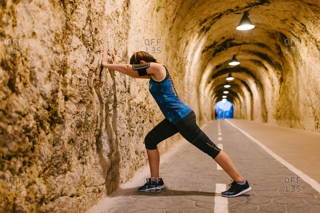 Side view of anonymous fit female athlete in sports clothes and armband standing leaned against rough wall while stretching legs during warm up in tunnel with artificial light