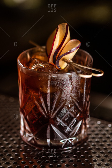 Shiny glass of alcohol cocktail with ice cubes garnished with fruit slices and placed on metal counter in bar