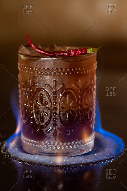 Flaming alcohol cocktail with ice cubes garnished with spicy chili and placed on metal counter in bar