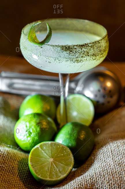 Glass of fresh mojito and bunch of ripe limes placed on rough sackcloth on table
