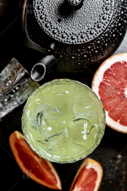 Top view of glass of cold alcohol beverage placed on table near pieces of grapefruit and teapot