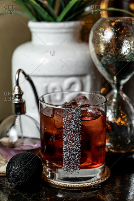 Glass cup of cold alcohol beverage decorated with poppy seeds and placed on table near vintage accessories
