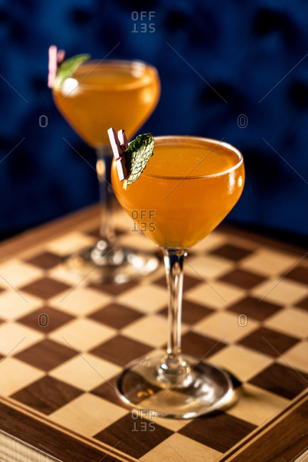 Glasses of orange alcohol drink with mint leaf placed on chessboard in bar