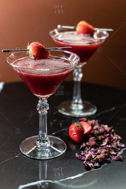 Glasses of sweet alcohol drink with strawberry placed near dried flower petals on table in restaurant