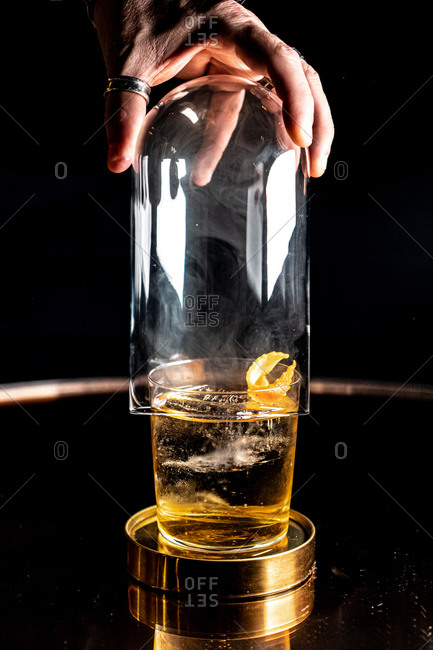 Unrecognizable bartender removing glass dome from cup of alcohol drink in dark room
