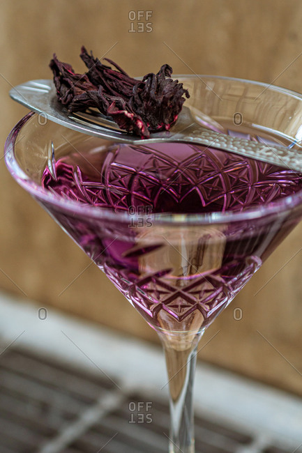 Closeup metal spoon with dried flower petals placed on glass goblet with violet cocktail in bar