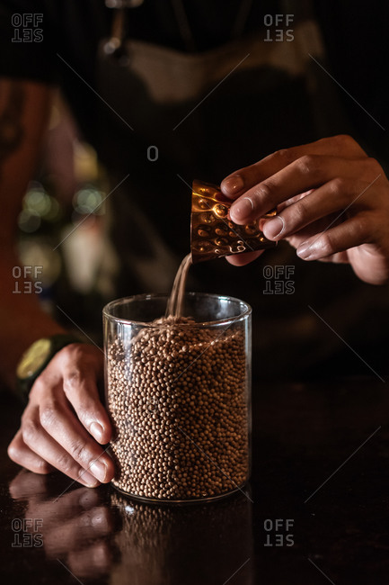 Anonymous man spilling coriander seeds from metal cup into glass jar in dark kitchen