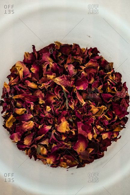 From above bunch of dried rose petals placed inside ceramic cup in kitchen
