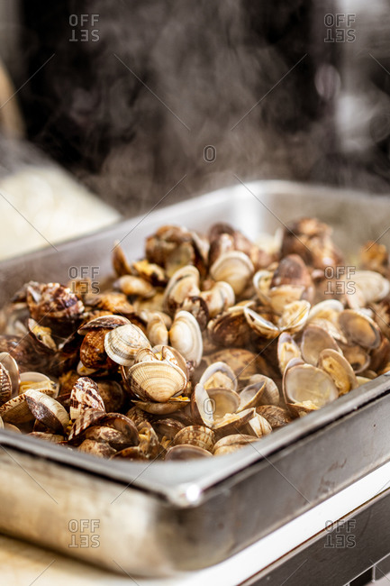Delicious fresh cooked clams on metal tray with white smoke in kitchen of luxury restaurant