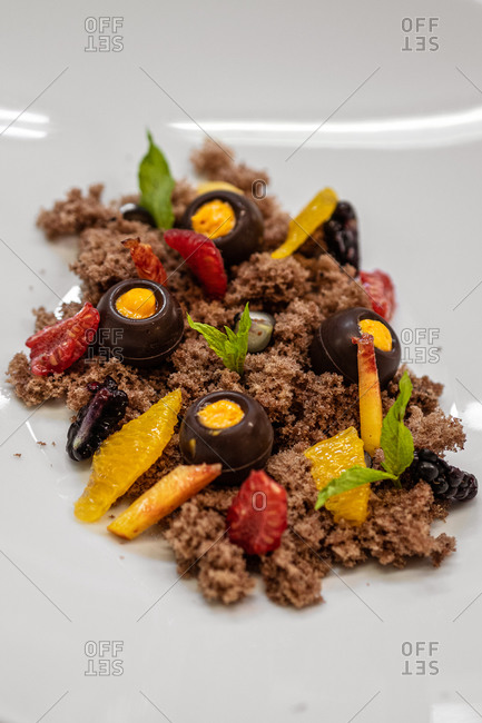 From above delicious chocolate dessert served with pieces of mango and strawberry and mint leaves on plate in restaurant