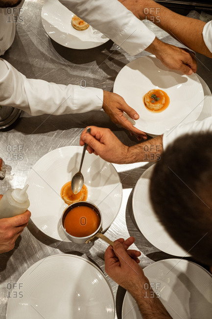 From above unrecognizable male chefs putting sauce on top of exquisite dish while working in luxury restaurant