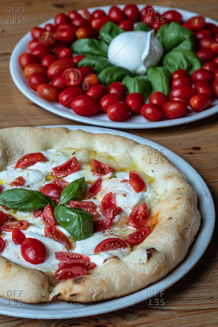 Round dish with yummy Pizza Margherita decorated with basil and dish with small oval tomatoes and basil placed on wooden table in Italian pizzeria
