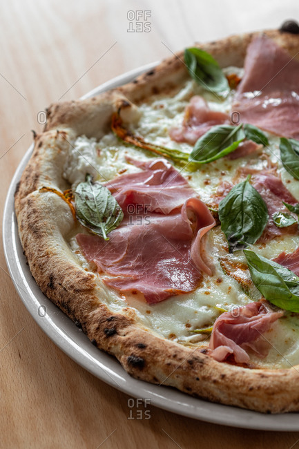 High angle of delicious Italian pizza with small tomatoes and charred cornicione served with ham and mozzarella and decorated with basil leaves placed on black dish on wooden table