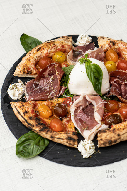 High angle of delicious Italian pizza with small tomatoes and charred cornicione served with prosciutto and mozzarella and decorated with basil leaves placed on black dish on linen tablecloth