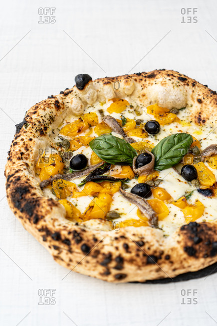 High angle of yummy crusty cheese pizza with sliced yellow tomatoes and olives decorated with basil leaves