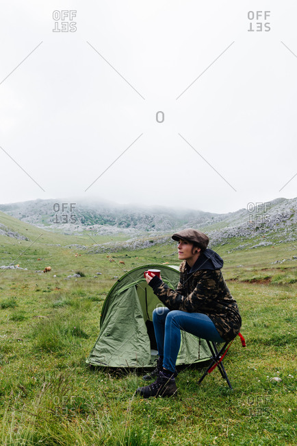 Full length content female traveler in jeans and warm khaki jacket sitting on folding chair near camping tent with cup of hot drink during camping in highlands looking away