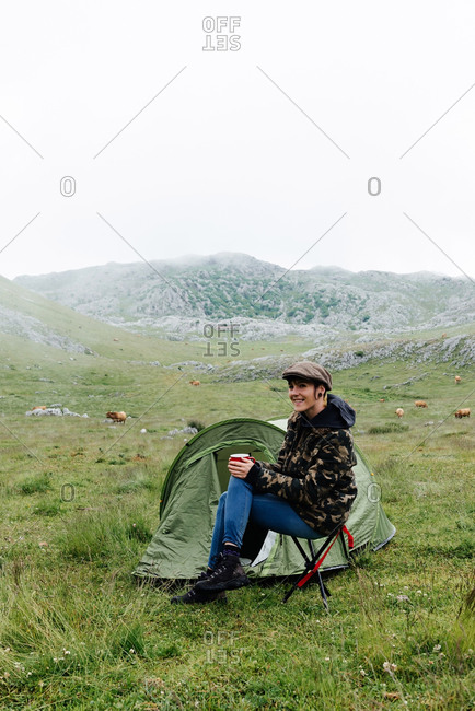 Full length content female traveler in jeans and warm khaki jacket sitting on folding chair near camping tent with cup of hot drink during camping in highlands
