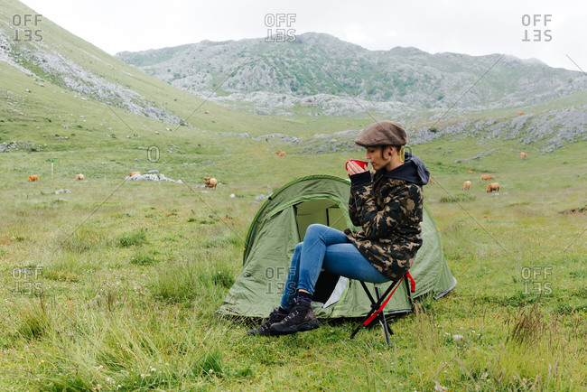 Full length content female traveler in jeans and warm khaki jacket sitting on folding chair near camping tent with cup of hot drink during camping in highlands with closed eyes
