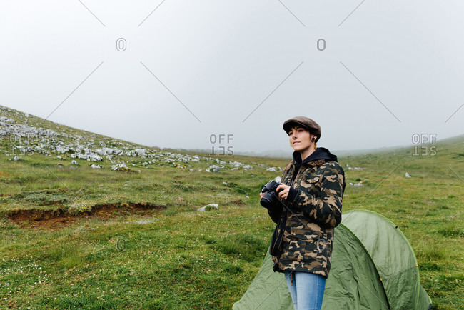 Positive young woman in outerwear with professional photo camera standing near camping tent in autumn countryside and looking away