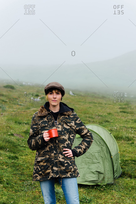 Content female traveler in jeans and warm khaki jacket standing near camping tent with cup of hot drink during camping in foggy highlands looking at camera
