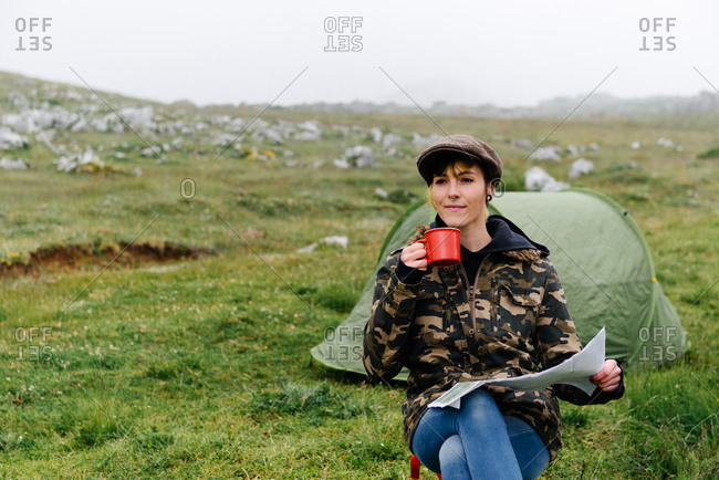 Concentrated female traveler with map sitting with legs crossed on folding chair against camping tent in autumn nature and looking away pensively