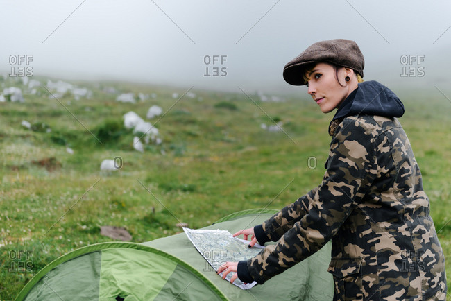 Side view positive female tourist in warm clothes and cap putting map on camping tent and navigating in location while looking away in foggy morning