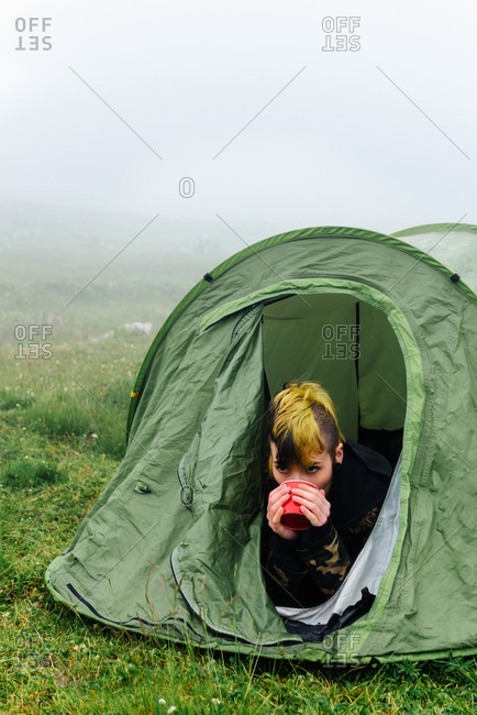 Dreamy female traveler lying in camping tent with cup of hot drink while spending weekend in nature in foggy morning
