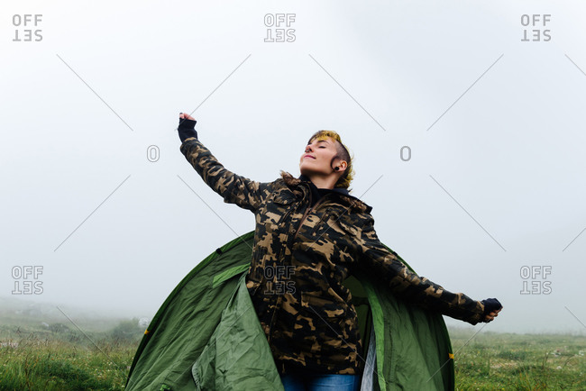 Positive female in warm clothes getting out of camping tent and stretching body during foggy morning in nature
