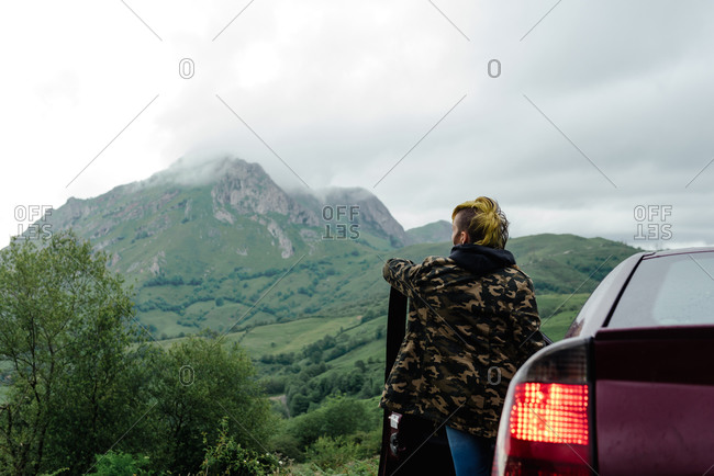 Back view of unrecognizable traveler in camouflage outerwear stopping on road and admiring view of mountain ridge during trip through countryside on cloudy day