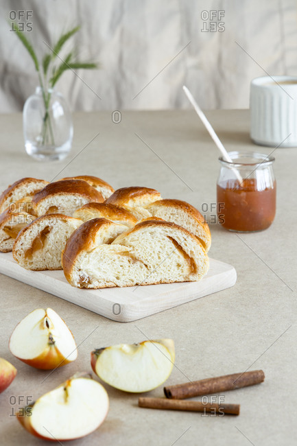 From above of fresh brioche made from butter dough with jam on wooden board next to glass jar of jam